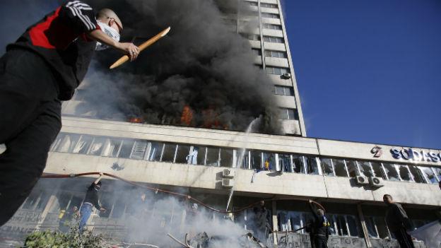 Demonstrant vor brennendem Hochhaus.
