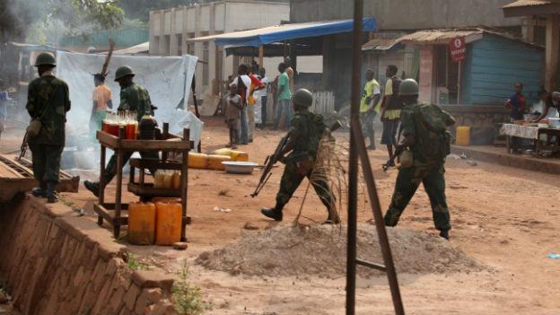 Bangui: Soldaten und Zivilisten laufen an Hütten vorbei.
