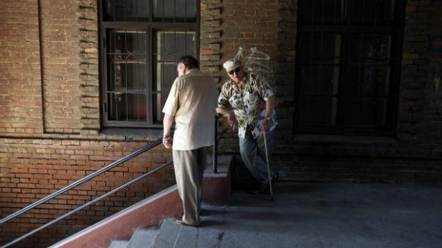 Zwei alte Männer sitzen vor einer MAuer in Wladiwostok.