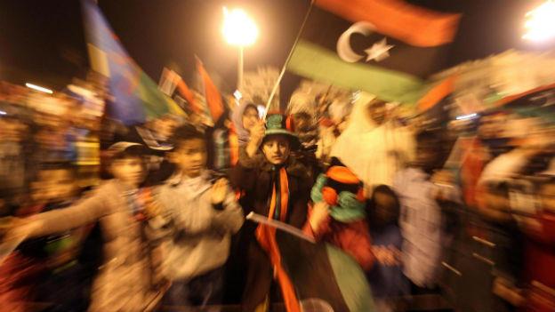 Nachtaufnahme von feiernden Menschen in Tripolis, die libysche Fahnen schwenken.