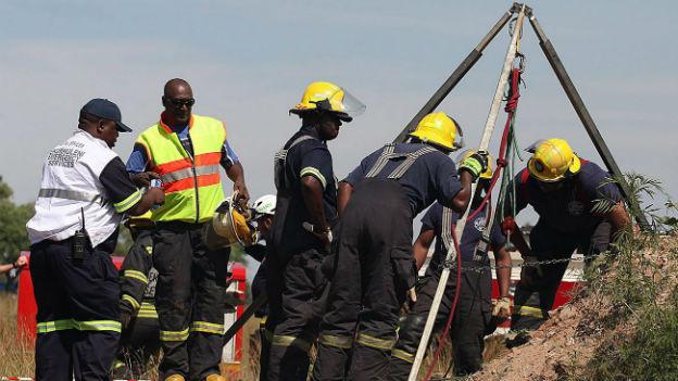 Rettungsarbeiter stehen um einen kleinen Kran, mit dem verschüttete Minenarbeiter geborgen werden sollen.