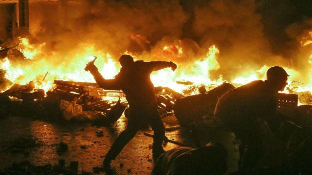 Demonstrant auf dem Maidan in Kiew wirft Brandsatz.
