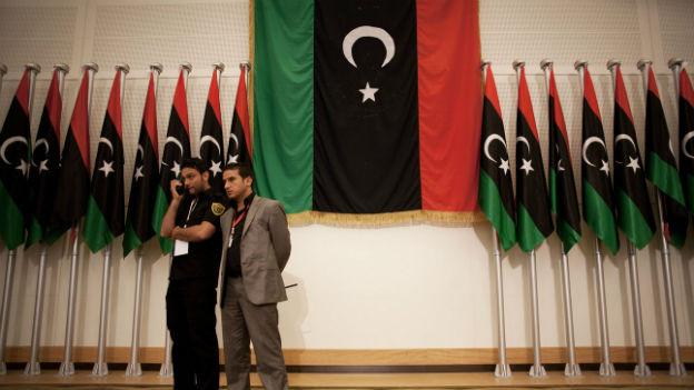 Zwei Sicherheitsleute stehen vor libyschen Flaggen.
