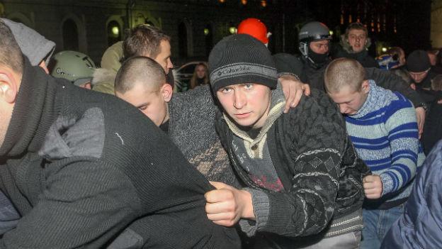Ukrainische Demonstranten, die leicht geduckt und in einer Einerreihe von der Polizei wegschreiten.