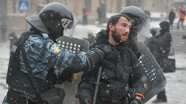 Ein ukrainischer Demonstrant wird von zwei Polizisten in Kampfmontour abgeführt.