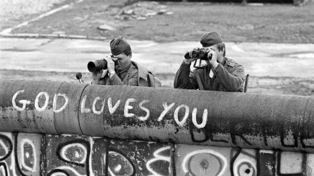DDR-Grenzposten spähen über die Mauer in Berlin.