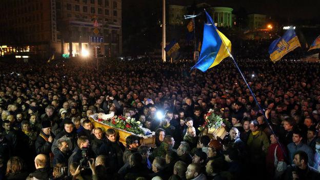 Riesige Menschenmenge nachts auf einem Platz rund um einen offenen Sarg, ukrainische Fahnen.