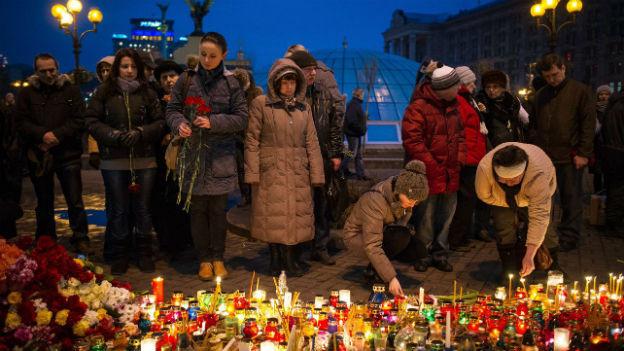 Menschen legen Blumen und Kerzen nieder für die Opfer der Proteste auf dem Maidan.