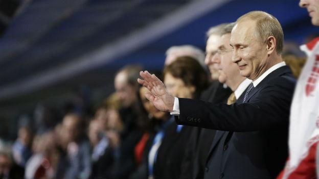 Seitliche Aufnahme von Wladimir Putin: Er hebt den linken Arm zu einer Gross- oder Winkbewegung.