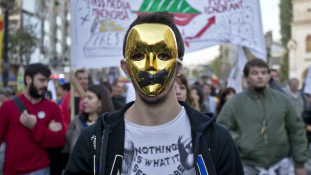 Ein Mann demonstriert mit einer Goldmaske gegen ein Bergbauprojekt in Rumänien.