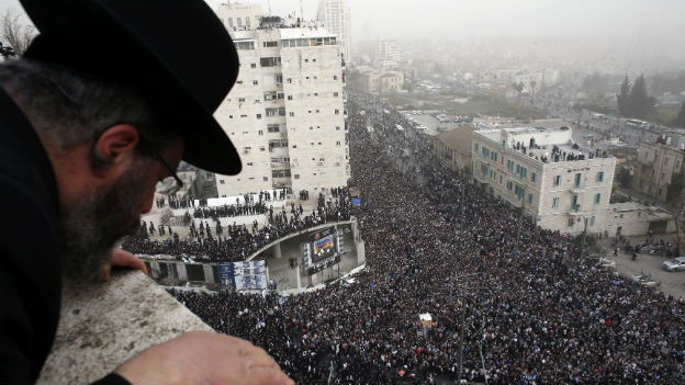 Ein orthodoxer Jude blickt von einem Hausdach auf die Massendemonstration in Jerusalem, wo tausende von ultraorthodoxen Juden demonstrieren.