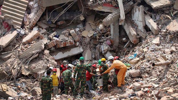 Arbeiter versuchen, zwei Leichen aus den Trümmern des eingestürzten Fabrikgebäudes zu bergen. Beim Zusammensturz am 24. April 2013 verloren 1129 Menschen ihr Leben.