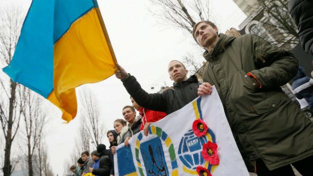 Mehrere Ukrainische Studenten schwingen Flaggen.