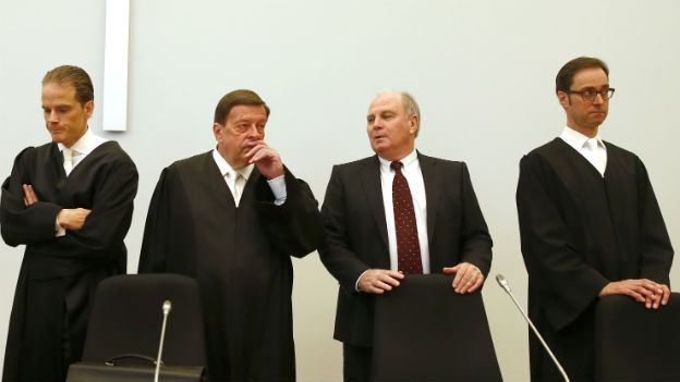Uli Hoeness mit seinen Anwälten Bernd Gross, Hanns Feigen und Markus Gotzens stehen vor einer weissen Wand. Alle vier tragen schwarze Anzüge, bzw. Roben.