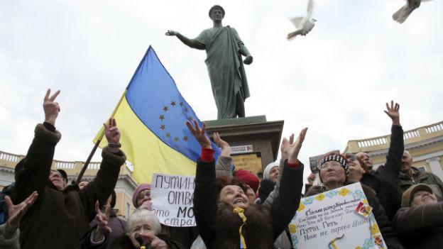 Demonstranten lassen vor einer ukrainisch-europäischen Flagge Tauben fliegen.