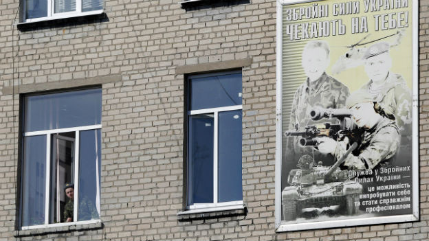 "A Ukrainian soldier looks out of the window of a regional military commissariat, with a placard reading, ""Ukraine's armed forces wait for you!"" during a visit by the Organization for Security and Co-operation in Europe (OSCE) mission in Donetsk, Ukraine, Thursday, March 13, 2014."