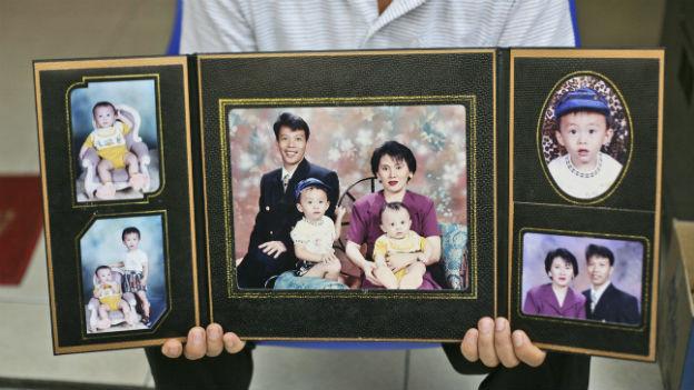 Angehöriger zeigt Bild von Opfer des Flugs MH370