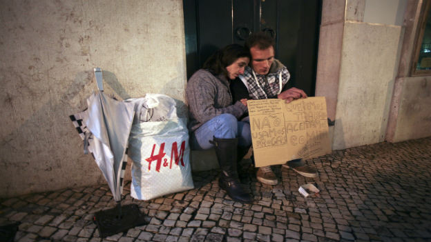 Ein Paar, das auf der Strasse sitzt und ein Plakat vor sich trägt, wo es um Hilfe bittet