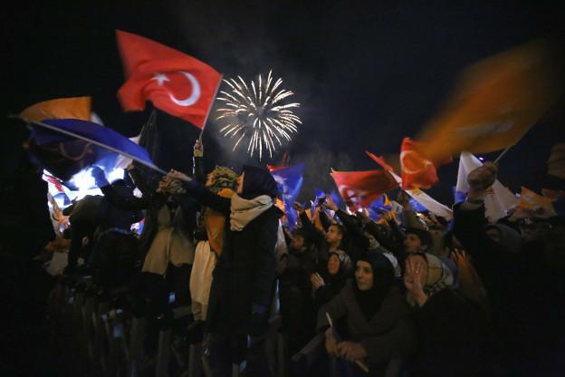 Menschen schwenken die Türkische Fahne und feiern damit den Wahlsieg der AKP, im Hintergrund Feuerwerk.