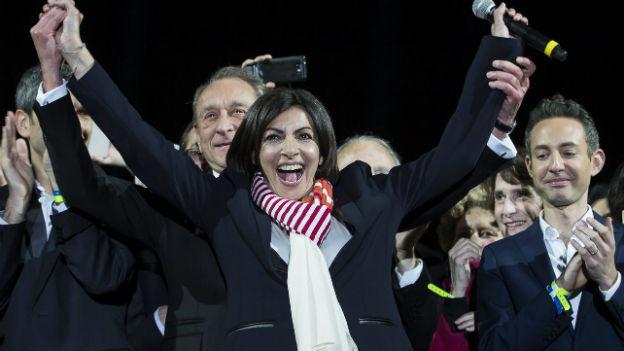 Anne Hidalgo hebt die Arme hoch und jubelt, umringt von zahlreichen Menschen: Die Sozialistin wurde zur neuen Pariser Bürgermeisterin gewählt.