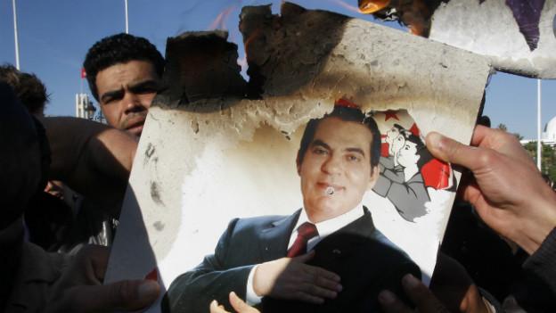 Wütende Demonstranten verbrennen 2011 ein Bild des gestürzten Diktators Ben Ali.