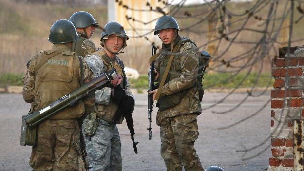 Vier Soldaten stehen schwer bewaffnet da.