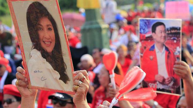 Anhänger der thailändischen Regierung demonstrieren für Yingluck Shinawatra und halten ein Foto von ihr in die Höhe.
