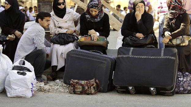Syrische Flüchtlingsfrauen warten vor ihren Koffern auf Aufnahme.