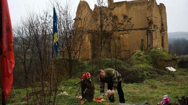 Ein Serbe legt vor einer Ruine Blumen am Grab eines gefallenen Landsmannes nieder.