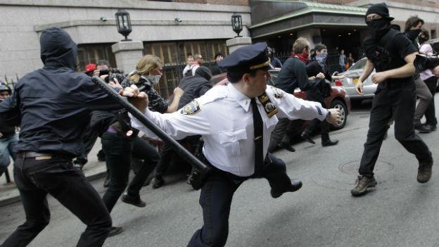 Archivfoto von 2011 aus der Occupy Wallstreet Zeit: Ein Polizist geht mit einem Schlagstock auf einen vermummten Demonstranten los.