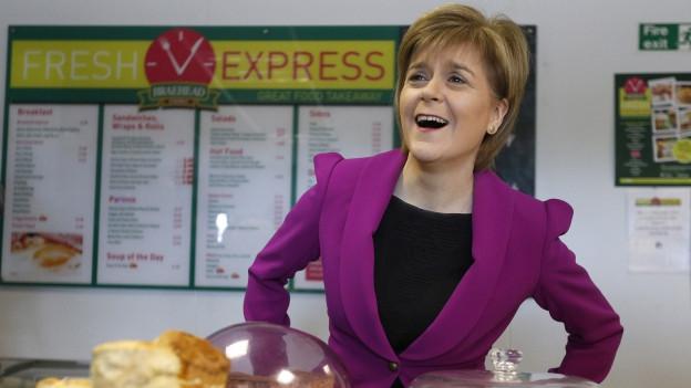 Nicola Sturgeon im violetten Blazer steht hinter einer Theke, auf der mehrere Kuchen stehen.