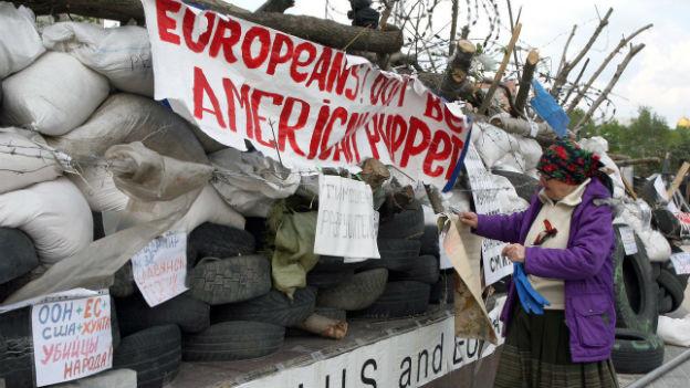 Ältere Frau in Donezk steht vor einer Mauer aus Reifen und Sandsäcken mit einem Transparenten und Plakaten.