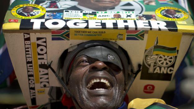 """Ein Mann trägt an einer Wahlveranstaltung für die Regierungspartei ANC in Südafrika einen riesigen Hut, auf dem das Wort """"Together"""" steht."""