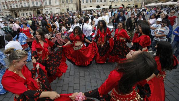Tanzende Romafrauen mit Zuschauern auf einem Prager Platz.