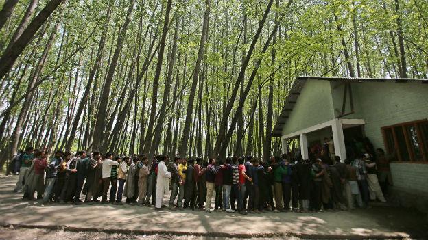 Inder stehen Schlange, um ihre Stimme abzugeben in den Parlamentswahlen.