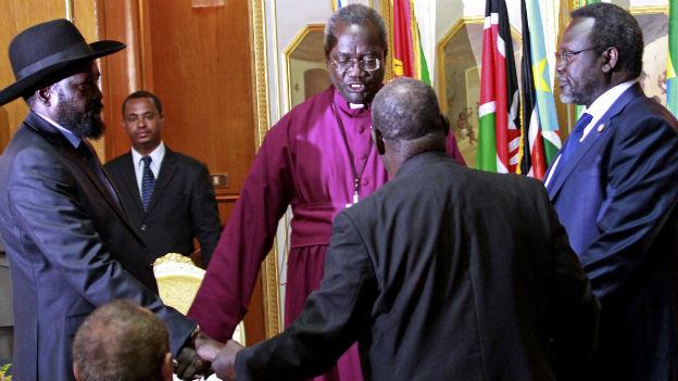 Salva Kiir, Riik Machar und zwei weitere Männer halten sich im Kreis an den Händen.