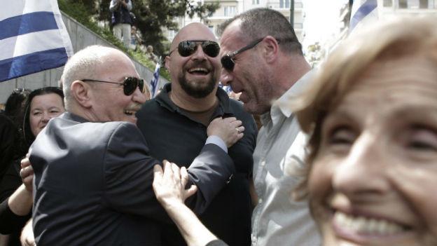 Drei lachende Männer mit Sonnenbrillen und eine Frau umarmen sich neben einer griechischen Flagge.