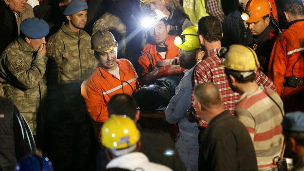 Zahlreiche Helfer bergen einen toten Grubenarbeiter.