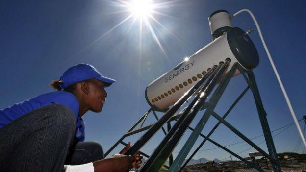 Ein Mann montiert ein Solarstrom-Modul auf einem Hausdach in Afrika.