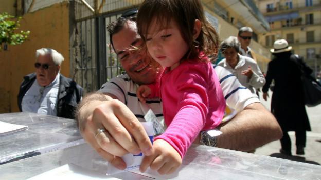 Ein Mann und seine Tochter werfen einen Stimmzettel in die Urne in Thessaloniki.