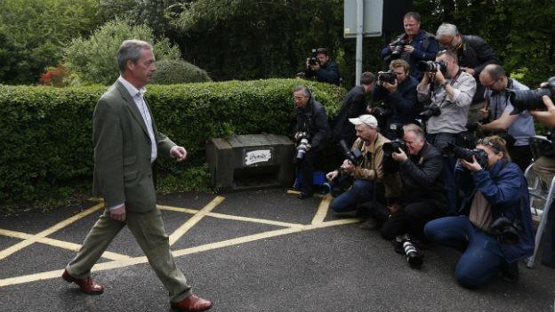 Der Britische Politiker und EU-Kritiker Nigel Farage schreitet zum Wahllokal, ein Dutzend Fotografen halten die Kamera auf ihn.