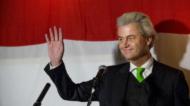 Geert Wilders, Rechtspopulist in den Niederlanden, steht vor einer bildfüllenden niederländischen Flagge und winkt.