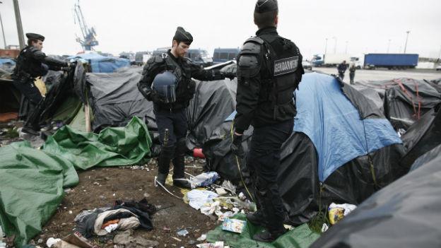 Drei Polizisten beim Einsatz in einem Flüchtlingscamp in Calais.