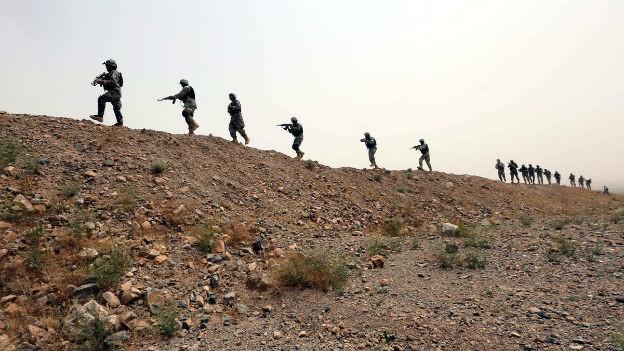 Weitwinkelaufnahme eines Hügels, auf dem afghanische Sicherheitskräfte in einer Kolonne marschieren.