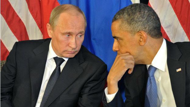 Nahaufnahme Putin und Obama, die nebeneinander sitzen und miteinander sprechen.