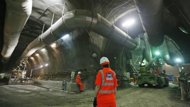 Ein Arbeiter auf der unterirdische Baustelle der Crossrail, der in den langen Tunnel blickt.