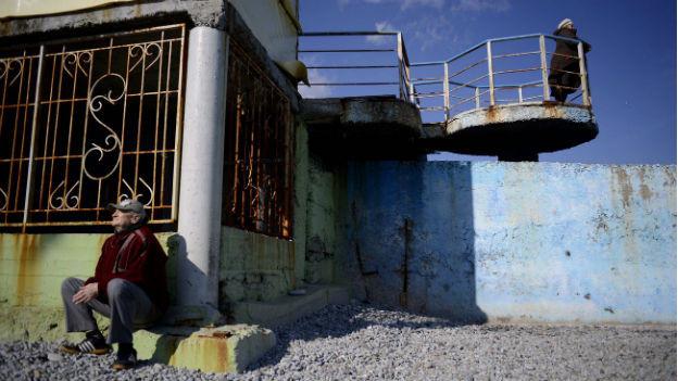 Zwei Krim-Bewohner vor einem heruntergekommenen Haus.
