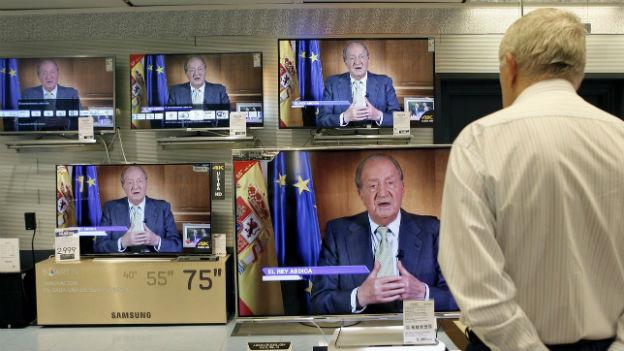Ein Mann verfolgt die Rede des spanischen Königs am Fernsehen.