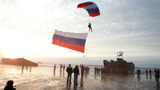 2 Fallschirmspringer mit rot-blau-weissen Fallschirmen landen an der Küste der Normandie