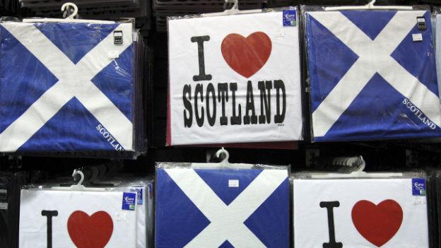 """Verpackte T-Shirts an einem Verkaufsstand, die die Schottische Flagge oder den Spruch """"I love Scotland"""" aufgedruckt haben."""